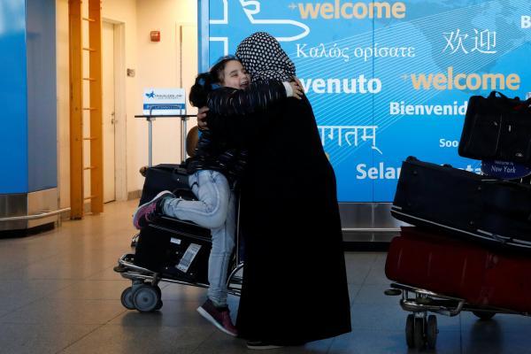 Viajantes estrangeiras se abraçam no aeroporto John F. Kennedy, em Nova York, neste sábado (4). (Foto: Brendan McDermid/Reuters)